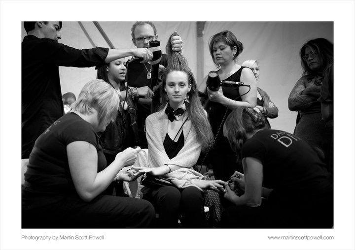 Angela (with a hairdryer on the right) backstage at a runway show.